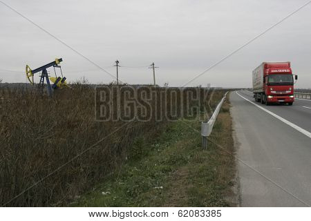 PLOIESTI, ROMANIA - NOV 8: A semi-trailer drives past a lone oil well near Ploiesti, Romania, on Thursday, November 8, 2007.