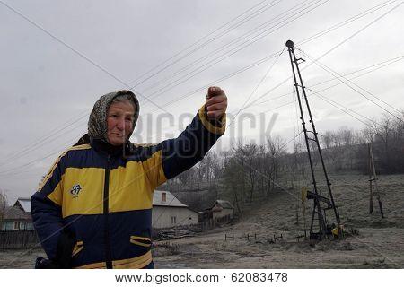 PLOIESTI , ROMANIA - NOV 8: An elderly woman gestures towards a field of pump jacks and oil storage tanks near Ploiesti, Romania, on Thursday, November 8, 2007.