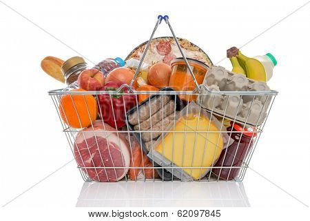 Studio shot of a shopping basket full of food including fresh fruit, vegetables, meat, pizza and dairy products. Isolated on a white background.