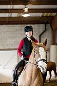 Teenage girl on horseback wearing helmet and safety vest in indoor arena poster