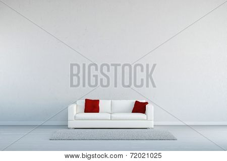 Couch with pillows and a carpet in front of a concrete wall