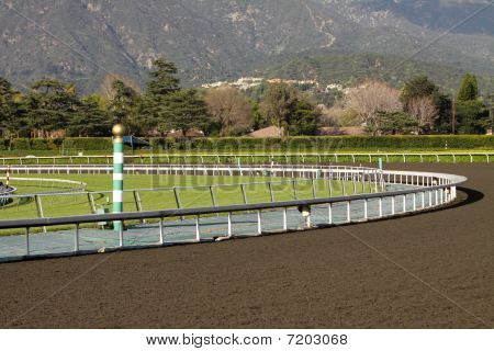 View of a horse racing track with mountains in background. Focus on green and white striped eighth pole. poster