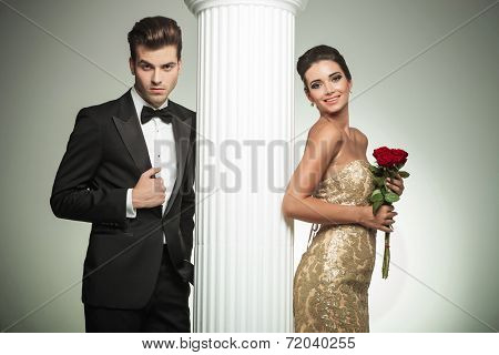 happy young married couple posing near column, woman in gown laughing poster