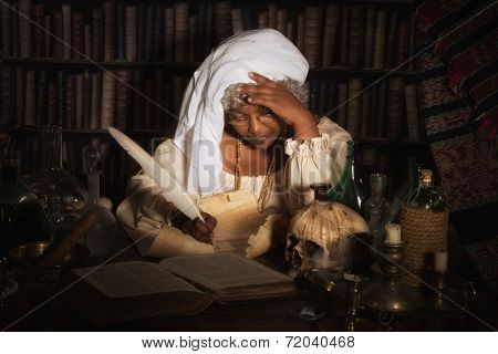 Dark image of a vintage alchemist writing in her books