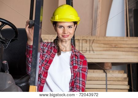 Portrait of confident female engineer wearing hardhat while standing by forklift in workshop