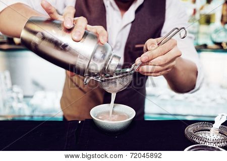Bartender is making cocktail at bar counter, toned image
