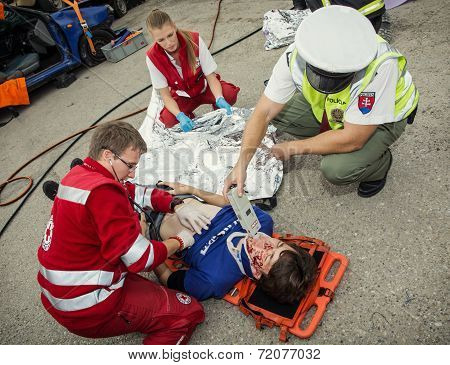 Paramedics Stabilizing The Patient. Policeman Makes The Breath Test For Alcohol.