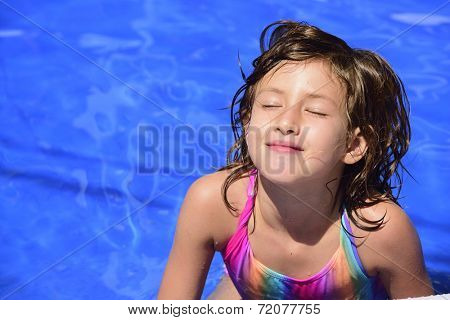Happy child relaxing in the pool sunbathing with eyes closed and copyspace