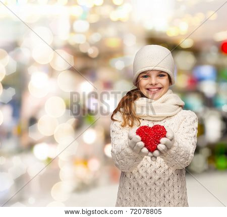 christmas, holidays, childhood, presents and people concept - dreaming girl in winter clothes with red heart over lights background