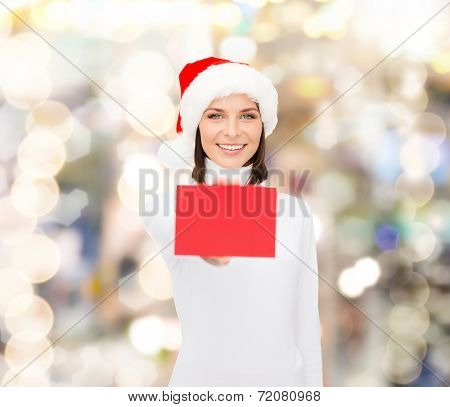 christmas, holdays, people, advertisement and sale concept - happy woman in santa helper hat with blank red card over lights background