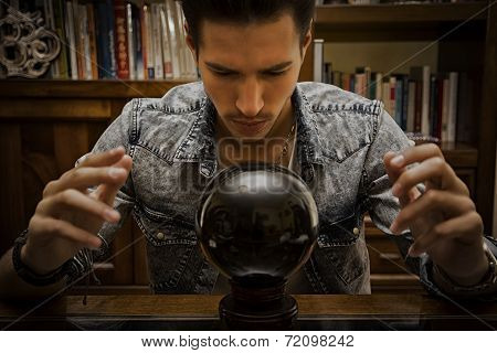 Young male seer predicting the future by looking into crystal ball
