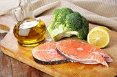 Raw salmon steaks broccoli lemon and olive oil on a wooden cutting board poster