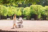 family, child and parenthood concept - happy mother walking with baby stroller in park from back poster