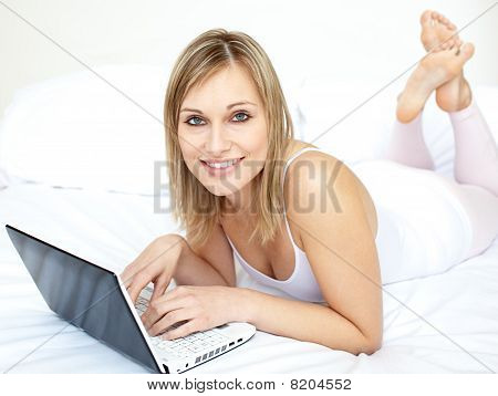 Attractive Woman Lying With A Laptop