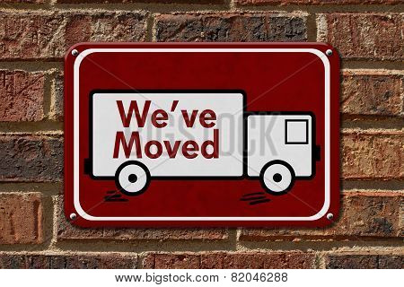 We have Moved Sign A red sign with the word We've Moved with a truck on a brick wall poster