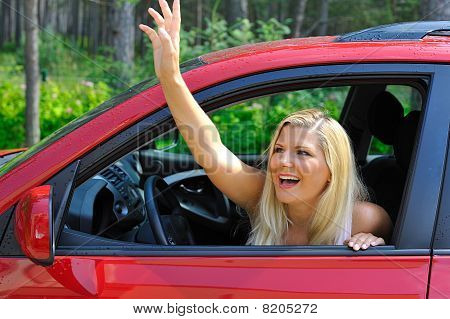 Beautiful Woman Driver In Red Shiny Car Outdoors Smiling And Waving With Hand
