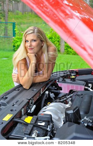 Young Beautiful Woman Standing Near Red Car And Looking Under Hood On The Engine And Other Car Detai