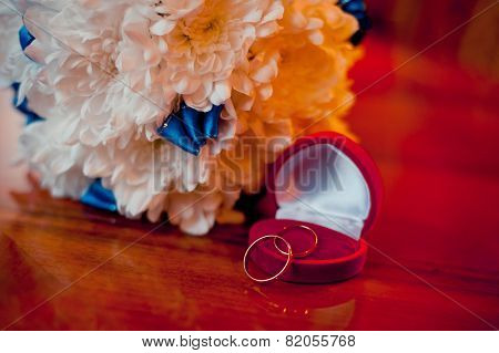 Wedding Rings On A White Background With A Bouquet Of Blue Ribbons