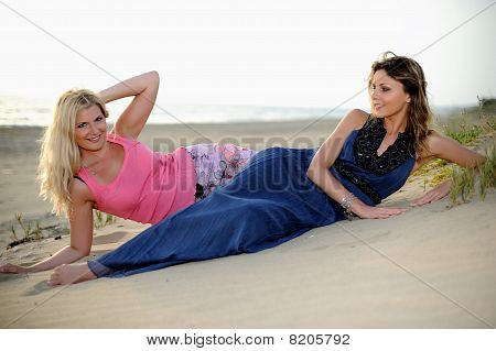Two Young Girls Friends Relaxing On The Beach Togather