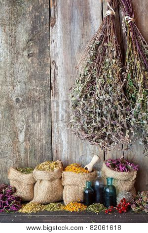 Healing herbs in hessian bags near rustic wooden wall herbal medicine. poster