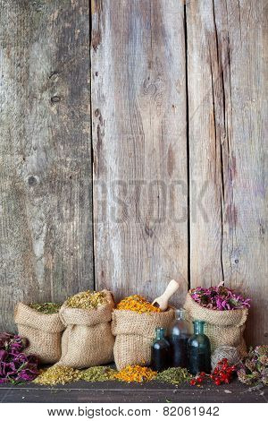 Healing herbs in hessian bags on old wooden background herbal medicine. poster