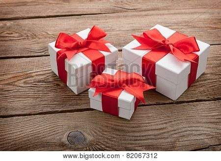 White Gift Boxes With Red Bows On The Old Board. Gift Concept