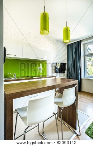 Green kitchenette and dining space in hotel room poster