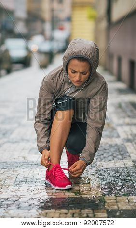 Woman Runner Kneeling Down To Tie Running Shoe In Rain