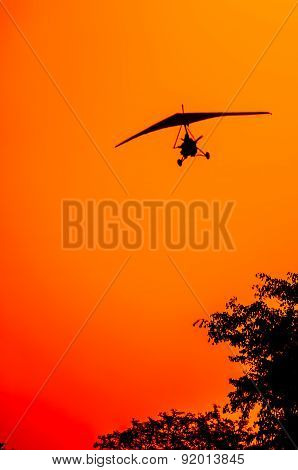 The silhouette of a microlite aircraft on final approach as it gets ready for landing over the tree tops as the sun is setting in a red orange and yellow sky. poster