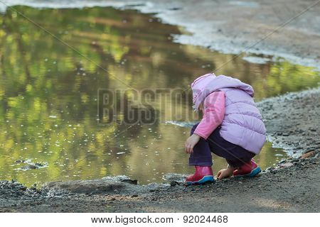 Tree Years Old Girl Looking For Pebbles On Big Summer Puddle Bank