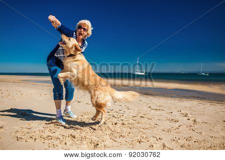 Happy older woman playing on the beach with golden retriever