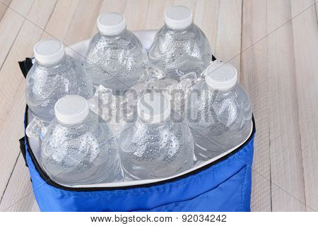 Closeup of six plastic water bottles and ice in a collapsible cooler on a white wood table. Horizontal format with copy space