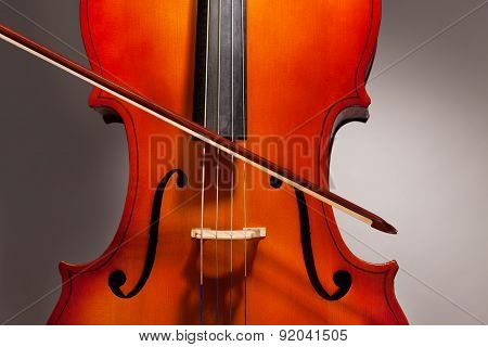 Violoncello with bow stick on the grey background