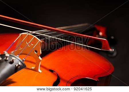 Violoncello with bow stick on black background