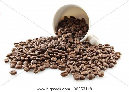 Overturned Cup Full Of Coffee Beans On White