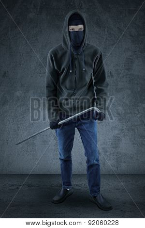 Burglar Holding A Crowbar To Steal