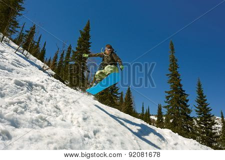 Snowboarder jumping through air with deep blue sky in background