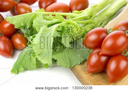 Tomatoes and fresh turnips on wooden background
