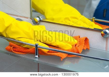 Woman's hand in rubber glove cleaning bath shelf. Cleaning concept.