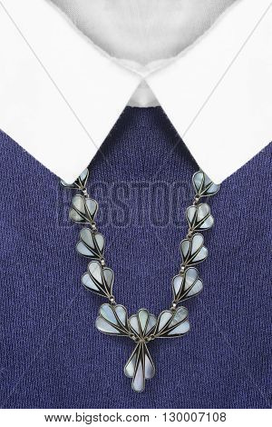 Vintage nacre necklace on blue pullover with white collar closeup