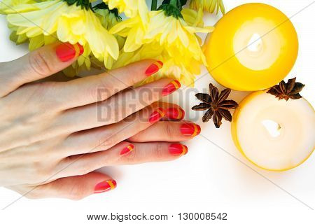 Skin care of a beauty female hands with pink and yellow striped nail art manicure. And yellow chrysanthemums with yellow two candles and two stars anise on the white background