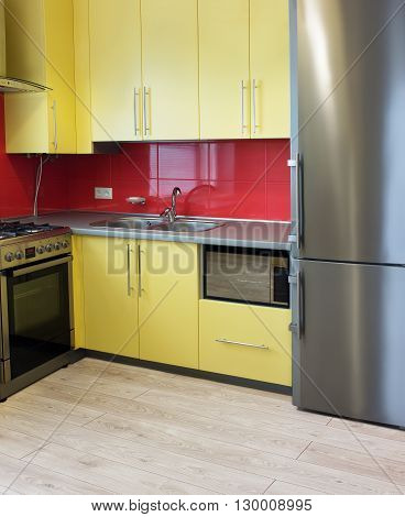yellow kitchen with cupboards with hinged doors topped with a grey worktops and fitted with appliances including refrigerator microwave oven extractor hood a wall with a red tile and floor with soft sand grey laminate