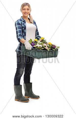 Full length portrait of a cheerful female gardener holding flowers isolated on white background