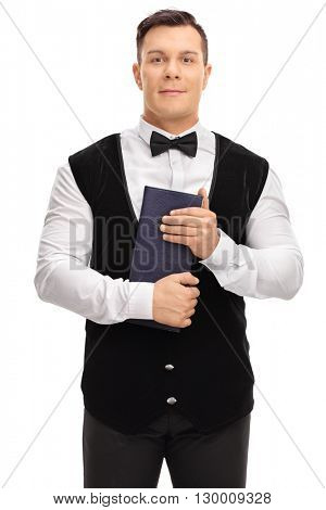 Vertical shot of a young waiter holding a menu and looking at the camera isolated on white background