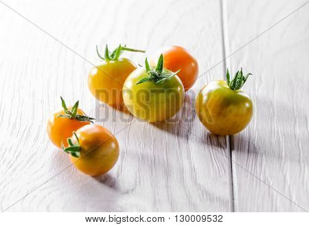 young cherry tomato on white wooden background