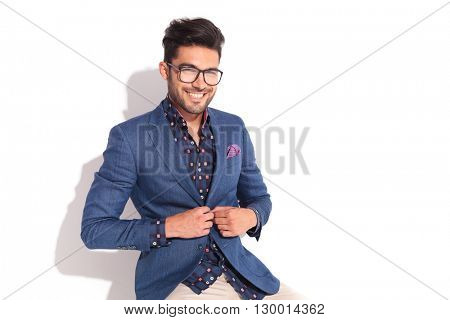 laughing young man unbuttoning his coat while seated in studio
