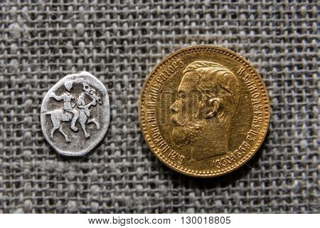 Two Russian coins - silver kopek of Ivan Grozny and gold five rubles of Nikolay Romanov.