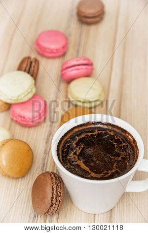 Cup of black coffee with french colorful macarons. Sweet delight. Vertical composition. Food and drink. Tasty macarons. Sweet food.