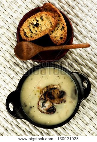 Delicious Homemade Mushrooms Cream Soup Decorated with Roasted Champignons in Black Iron Stewpot with Herb Crunchy Bread and Wooden Spoon closeup on Wicker background