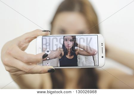 Beautiful young woman photographing herself with phone sitting in sofa